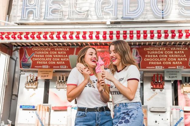 Jovens amigos comendo sorvete no parque de diversões