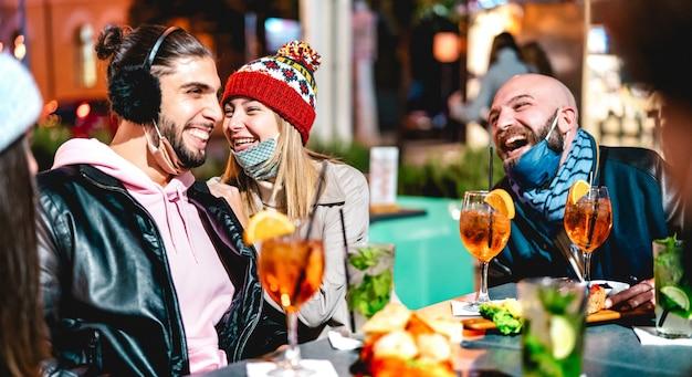 Jovens amigos conversando em um bar de coquetéis de inverno ao ar livre usando máscara aberta