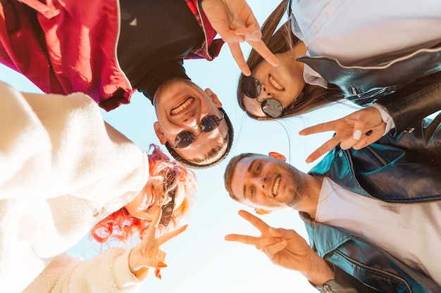 Jovens amigos de pé em círculo e mostrando o gesto de paz