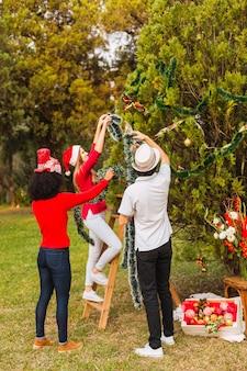 Jovens amigos decorando a árvore de natal
