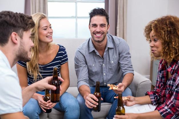 Jovens amigos desfrutando de cerveja e pizza no sofá em casa