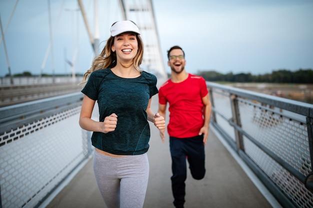 Jovens amigos desportivos saudáveis a correr e a correr ao ar livre