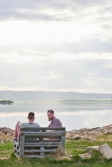 Jovens amigos do sexo masculino sentados em um banco de madeira no fundo do lago pitoresco, conversando e curtindo uma noite tranquila de verão ao ar livre