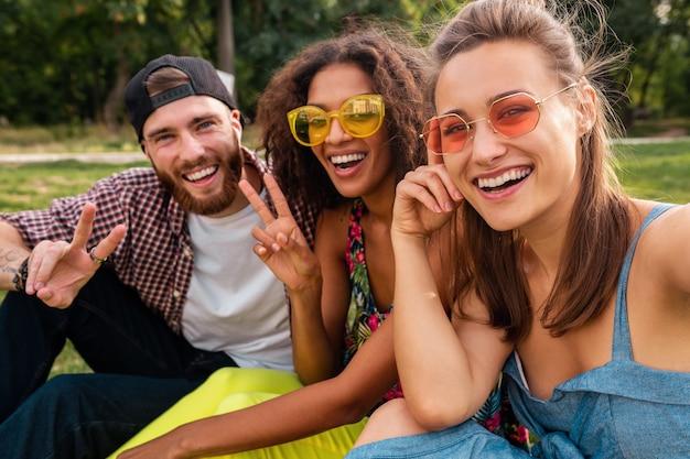 Jovens amigos elegantes e felizes sentados no parque, fazendo selfie
