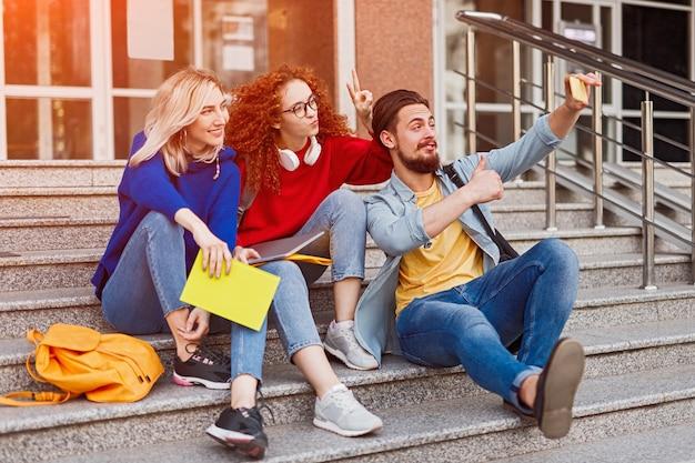 Jovens amigos em roupas casuais tirando selfie