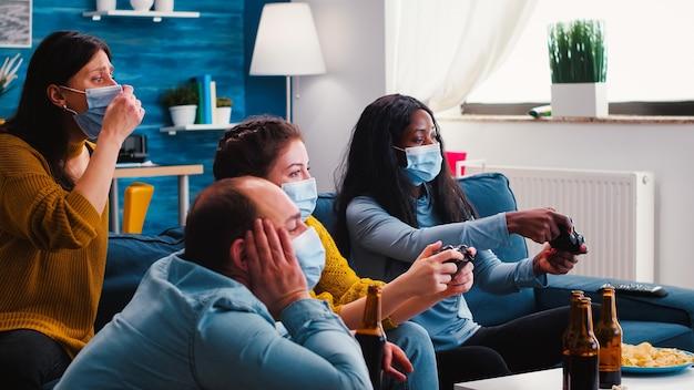 Jovens amigos engraçados com máscaras segurando controles jogando videogame em casa durante a nova festa normal