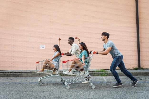 Jovens amigos felizes correndo com carrinhos de compras