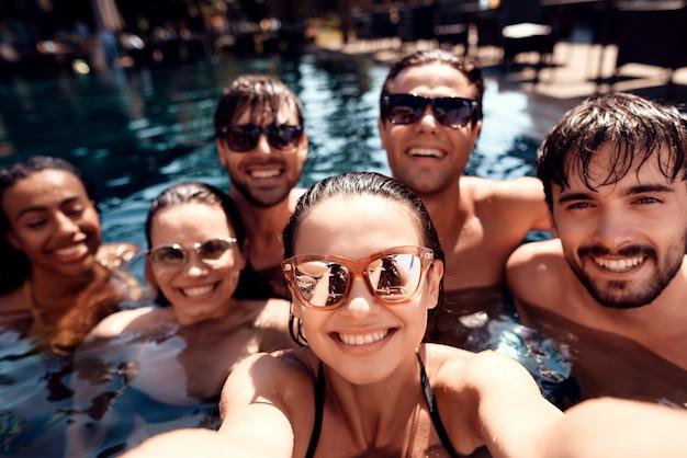 Jovens amigos felizes fazem selfie na piscina.