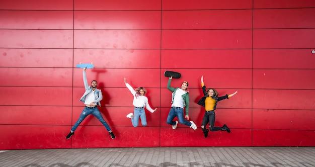 Jovens amigos felizes pulando na frente de um fundo de parede vermelha