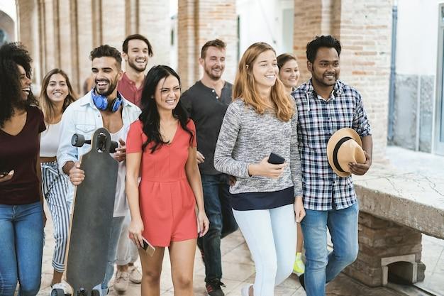 Jovens amigos felizes se divertindo juntos ao ar livre na universidade - foco principal no rosto do homem no centro