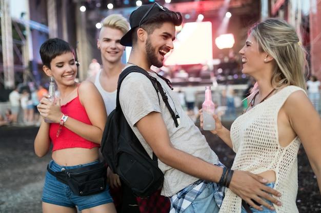Jovens amigos felizes se divertindo no festival de música