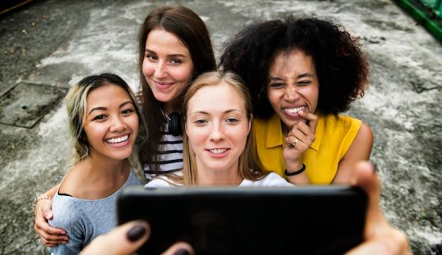 Jovens amigos femininos adultos tirando uma selfie de grupo