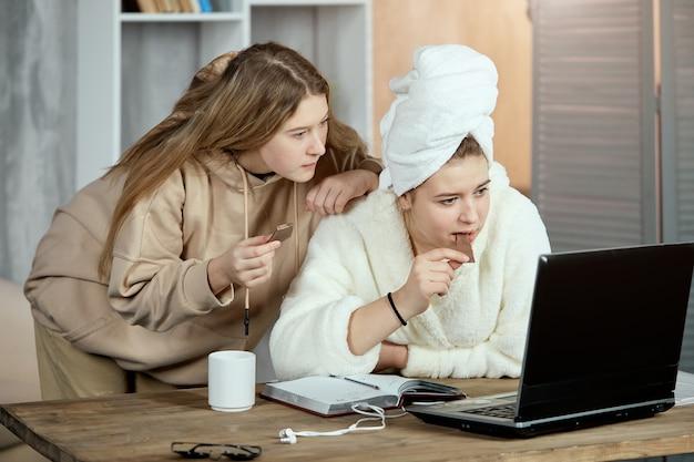 Jovens amigos gostam de assistir filmes ou programas de tv em um laptop com chocolate na mão