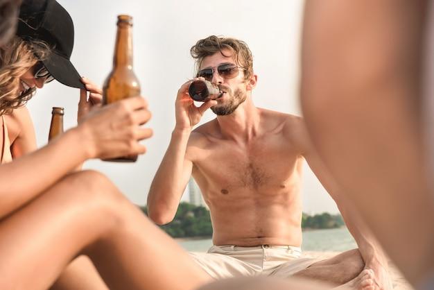 Jovens amigos gostavam de tomar uma bebida na praia