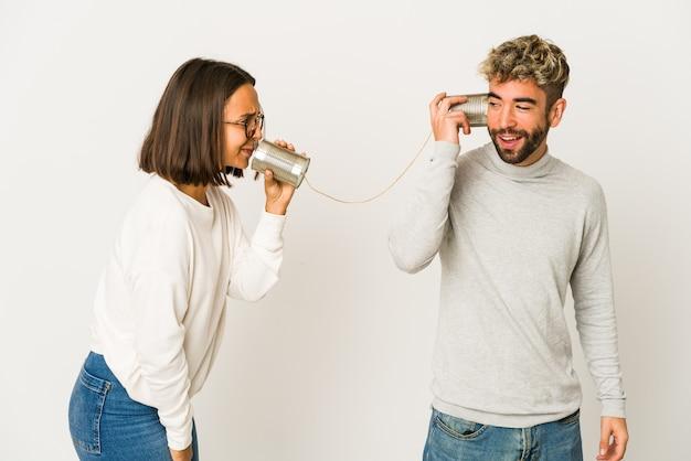 Jovens amigos hispânicos conversando através de um sistema de lata parecem de lado sorrindo, alegres e agradáveis.