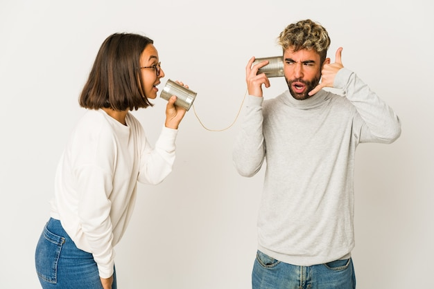 Jovens amigos hispânicos falando através de um sistema de lata, mostrando um gesto de chamada de celular com os dedos.