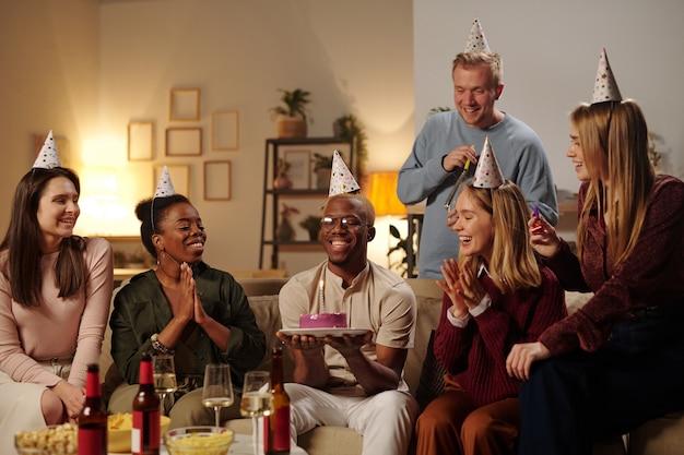 Jovens amigos interculturais felizes parabenizando um africano sorridente por seu aniversário e batendo palmas enquanto olham para um bolo delicioso