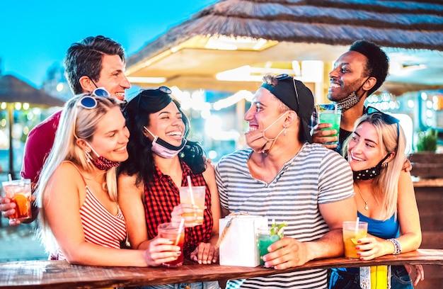 Jovens amigos internacionais conversando no bar de praia com máscara facial aberta