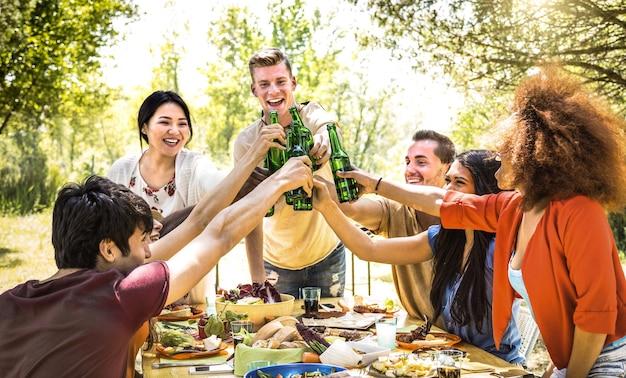 Jovens amigos multirraciais brindando em uma festa de churrasco no jardim