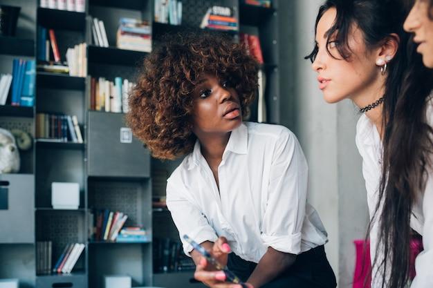Jovens amigos multirraciais discutindo juntos no escritório moderno e usando smartphone