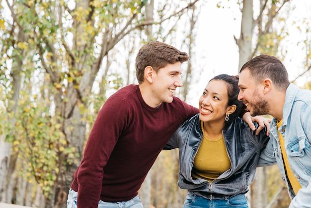 Jovens amigos multirraciais em pé com as mãos nos ombros