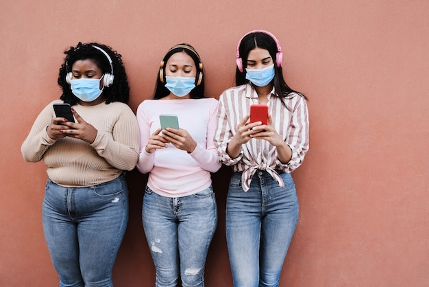 Jovens amigos multirraciais felizes usando máscaras de segurança enquanto usam telefones celulares ao ar livre