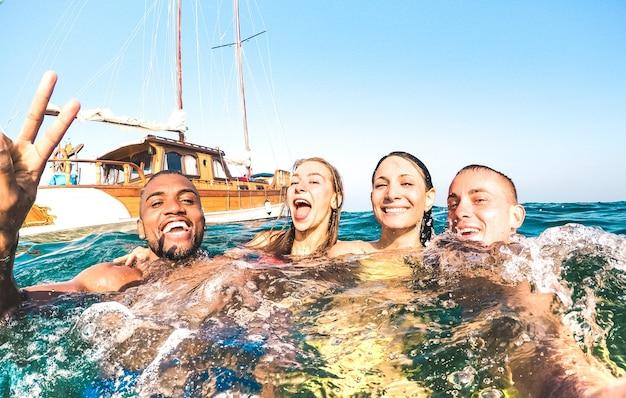 Jovens amigos multirraciais tirando selfie e nadando em uma viagem de barco à vela pelo mar