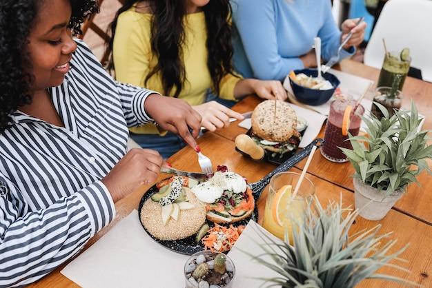 Jovens amigos multirraciais tomando café da manhã ao ar livre no terraço do restaurante - foco na mão direita da garota africana