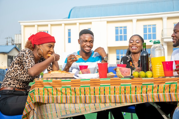 Jovens amigos negros comendo uma fatia de pizza e outros alimentos em um piquenique