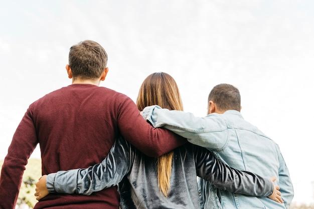 Jovens amigos próximos abraçando no dia brilhante
