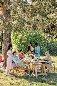 Jovens amigos relaxantes sentados e de pé ao lado da mesa servida sob um pinheiro enquanto conversam, comem comida caseira e aproveitam o dia de sol