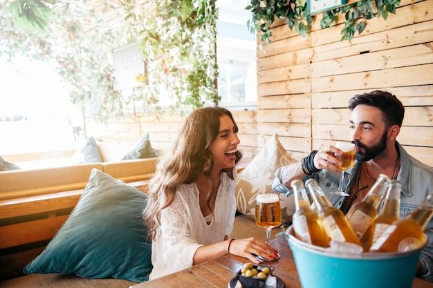 Jovens amigos rindo e bebendo