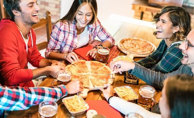 Jovens amigos rindo genuinamente enquanto comem pizza em casa na reunião de família