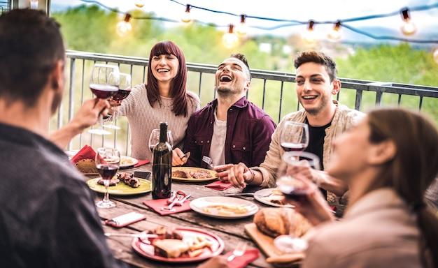 Jovens amigos se divertindo bebendo vinho tinto em um jantar na varanda da cobertura