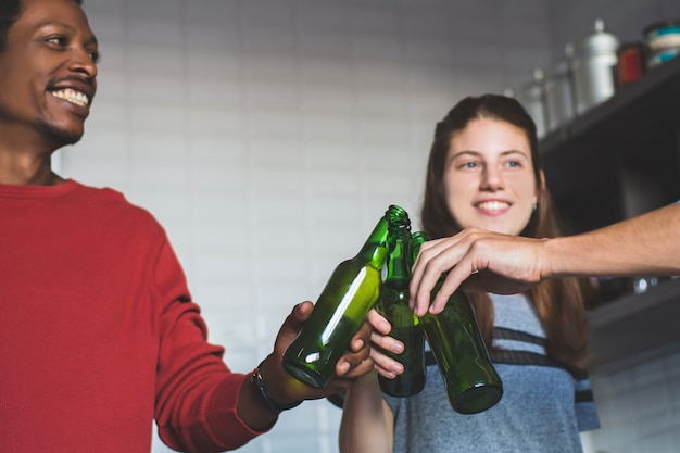 Jovens amigos se divertindo com garrafas em casa.