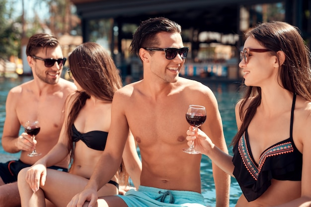 Jovens amigos sorridentes bebendo vinho à beira da piscina