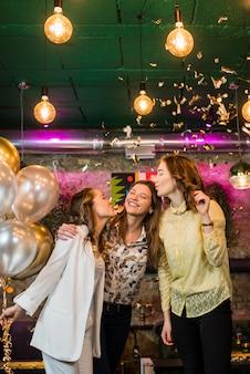 Jovens amigos sorridentes dando beijo para sua amiga na festa