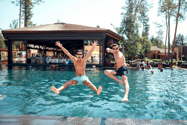 Jovens amigos sorridentes pulando na piscina