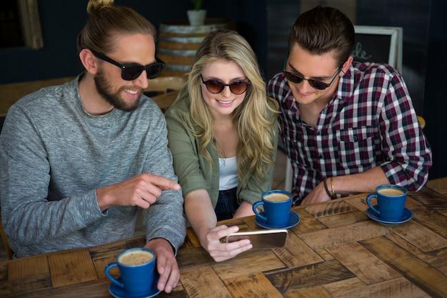 Jovens amigos sorridentes usando um telefone inteligente na mesa de um café