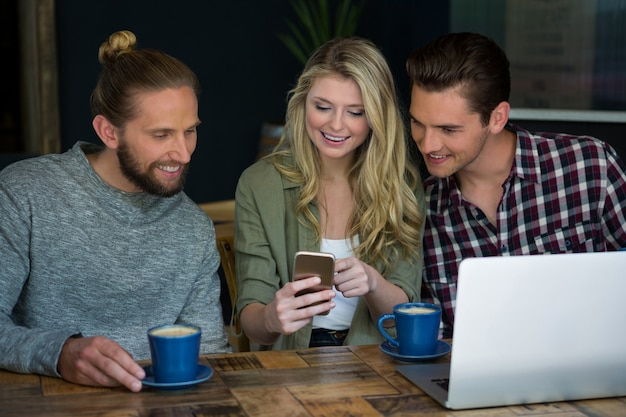 Jovens amigos sorridentes usando um telefone inteligente na mesa do refeitório