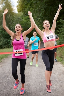 Jovens amigos terminando para uma maratona