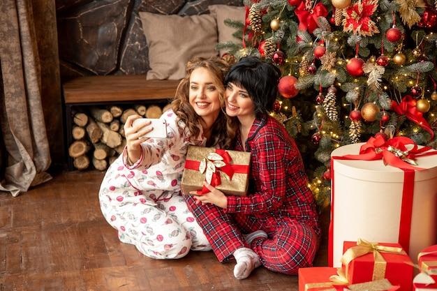Jovens amigos tirando auto-retrato com smartphone na véspera de natal. eles estão sentados em pð ° jamas perto da árvore de natal decorada com presentes.