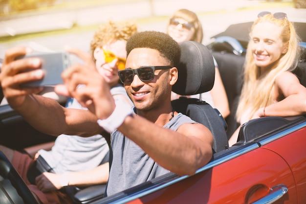 Jovens amigos tirando uma selfie em um carro cabriolet