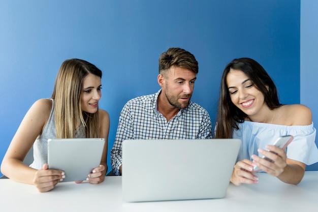 Jovens amigos trabalhando com dispositivos