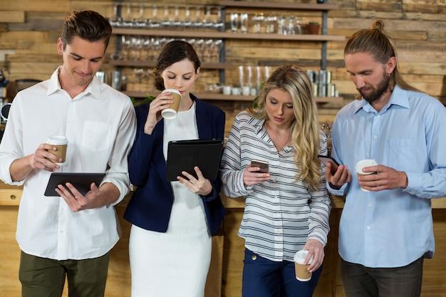 Jovens amigos usando tablet digital e telefone celular