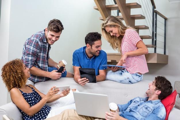 Jovens amigos usando tecnologias modernas no sofá