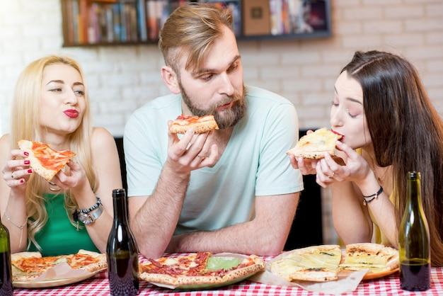 Jovens amigos vestidos casualmente com camisetas coloridas almoçando com pizza e cerveja em casa