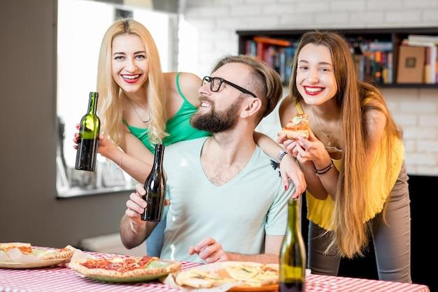Jovens amigos vestidos casualmente com camisetas coloridas se divertindo comendo pizza e bebendo cerveja em casa