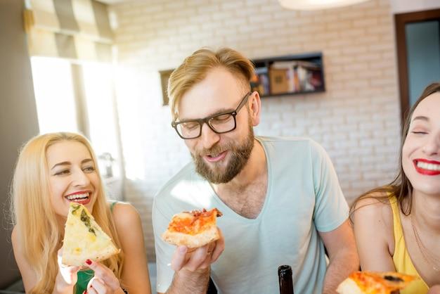 Jovens amigos vestidos casualmente com camisetas coloridas se divertindo comendo pizza em casa