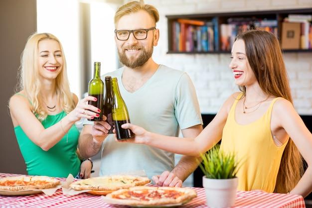 Jovens amigos vestidos casualmente com camisetas coloridas se divertindo em casa batendo garrafas com cerveja e pizza